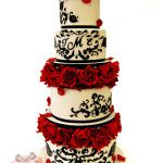 Inspired by our red rose damask wedding cake, this four tier cake includes rose separators, detailed black damask patterns and a monogram for the bride and