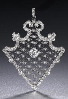 A Belle Époque diamond brooch/pendant, circa 1910. The articulated triangular openwork plaque
