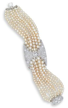A NATURAL PEARL, PEARL AND DIAMOND BRACELET  CENTERING UPON AN OLD EUROPEAN-CUT DIAMOND WITHIN A PAVE-SET OLD EUROPEAN-CUT DIAMOND PLAQUE OF GEOMETRIC MOTIF, JOINED BY NINE STRANDS OF ROUND CREAM AND WHITE PEARLS MEASURING APPROXIMATELY 3.6 - 5.9 MM ON EITHER SIDE TO THE SINGLE-CUT DIAMOND CLASP, MOUNTED IN PLATINUM, 17.2 CM LONG