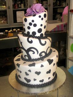 Charly's Bakery CT SA:3-tier Mad Hatter wedding cake covered in white fondant decorated with black fondant hearts, twirls & polka dots & lilac floppy roses on top by Charly's Bakery, via Flickr