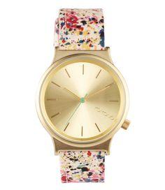 Een horloge van het merk Komono uit de wizard print series met een lichte band met bloemen