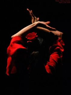 Red. Her arms dance, castanets clap, hands and feet click punta to heel, in a synchronized fury.