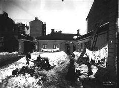 """Pieni Roobertinkatu 4–6 talvella 1907. Maalarimestari Löfströmin vaimo Selma hakee vettä pihan yhteisestä vesipostista. Talvella """"kraana"""" piti suojata hyvin, ettei se päässyt jäätymään. Kuva: Signe Brander."""