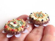 Miniature fruit cake, 1 inch scale, with kiwis, bananas, grapes, cherries and apricots. Very detailed, made of polymer clay. Each element is hand made and hand painted before assembling and covered with a delicious looking glossy jelly. Two variations (see below). A perfect accent