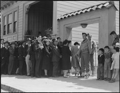 """Japanese family heads and persons living alone, form a line outside Civil Control Station located in the Japanese American Citizens League Auditorium at 2031 Bush Street, to appear for """"processing"""" in response to Civilian Exclusion Order Number 20, San Francisco, 25 April 1942. From Central Photographic File of the War Relocation Authority. Public domain via Wikimedia Commons."""