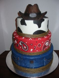 I love the combination of blue jeans, red bandanas, and cow print for a western themed party.  The cake is too cute!