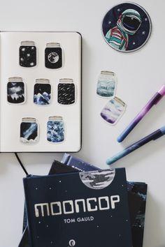 Caderno pontado da cícero, adesivos de potinhos com elementos de galáxia e universo e canetas em tons de galáxia.  #stationery #galaxy #melinasouza