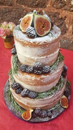 Three tier naked wedding cake for outdoor summer wedding, lemon cake blackberry jam and buttercream. Decorated with fresh fruit - figs, blackberries, rosemary.