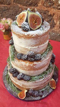 Three tier naked wedding cake for outdoor summer wedding, lemon cake blackberry jam and buttercream. Decorated with fresh fruit - figs, blackberries, rosemary.