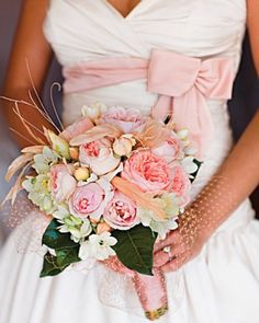 This bouquet by Floracopia at Soolip, matches the pink sash on the bride's gown, thanks to blush roses, lisianthus, and star-of-Bethlehem.