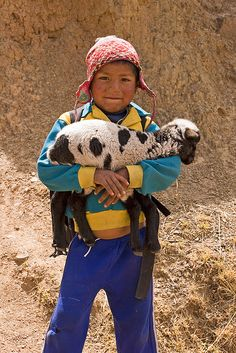 A young boy from #peru holding a lamb.