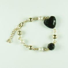 Pulseira com bolas douradas, pérolas, bola de acrílico facetada preta e coração de acrílico facetado preto.