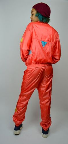Awesome 1980s track suit! Done in a bright coral/pink soft polyester material. Elastic stretch at cuffs & waistline. Zipper front, high collar. Two pockets on chest, and at sides. ixspa and star patch on chest. Both pieces are fully lined in a super soft cotton. Elastic stretch at waistline, with drawstring. Pockets on hips of pants. Zippers at ankles. Super comfortable!  SIZE: Small LABEL: Small BRAND: ixspa by Jamie Sadock  Very Good Vintage Condition: ixspa logo on left leg. Snap ...