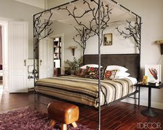 In the master bedroom, the Casamidy canopy bed has a  velvet-upholstered headboard and is dressed in Anichini  linens; the sconces and side table are vintage, and a vaulting horse serves as a bench.