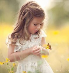 Children's outdoor photography, pretty little girl in the field of flowers with a butterfly landing on her arm