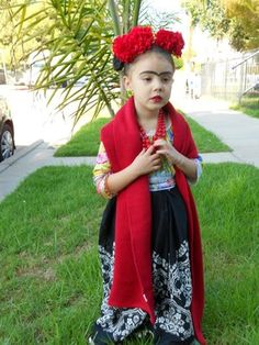 Thrift store-friendly Frida Kahlo costume: colorful, floral dress or skirt and scarf, big necklace, hot glue flowers on a headband