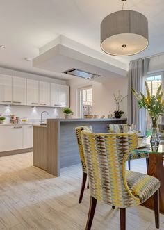 Luxurious open plan kitchen -dining with doors to the garden and modern high end wooden furniture in an elegant grey yellow decor.