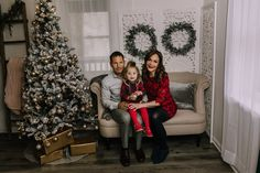 holiday mini session photo shoot christmas family neutral greenery garland tree lights screen sofa couch hugging red black dress
