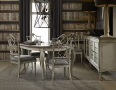Arabella projects a Modern French look by combining a serene white finish on maple veneer with crackle and champagne shimmer with heavily waxed aluminum tops and eglomise (painted glass). Photo: Hooker Furniture.