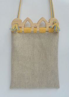 This piece is inspired by wooden purse frames found in the Viking Age trading settlement of Hedeby (Haithabu). Only the frames have survived to the modern era, so the rest of the bag is based on conjecture, and bags made by the Sami people. The strap and trim are made in the style of a tablet woven band found in the Oseburg ship burial (834 AD).