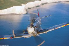 Splendid sight: Spitfire AR614 tears through the sky over the white cliffs of Dover.