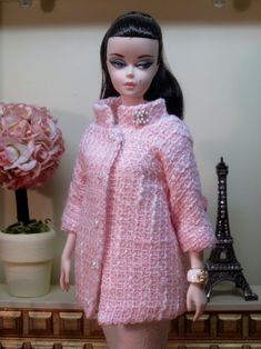 A new coat design inspired by Chanel, with a slim sheath. The coat has an A-line shape and is made from candy pink wool bouclé woven with white. It has a funnel neck and 3/4 length sleeves. The …