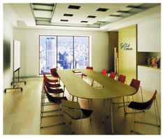 Modern Office Meeting Room Design With Oval Table Red Chairs Laminate Flooring And Wide Glass Window