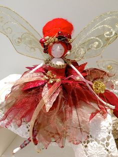 Meet Firecracker - one of my luxury Ooak Fairy Christmas Tree Top fairies. She is dressed in a gown of glittered petals which are arranged over layers of tulle and organza. Her bodice is edged with gold brocade. Her vibrant red merino wool hair is elegantly coiffured into a glorious beehive and dressed with gorgeous red berries and gold bullion. In her hand she carries her jewelled wand. Her legs are painted in the signature striped stocking of the Fabulous Fairy Creations. Her handmade…