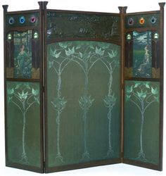 A three panel oak Arts & Crafts screen. Inset with painted and embroidered panels, coloured bull-nose leaded glass set into copper with gesso, mother of pearl and stencilled linen. Circa 1900.