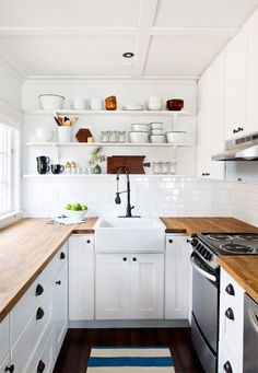black hardware, white cabinets, stainless appliances, wood counters, open shelving, cabinets to the ceiling
