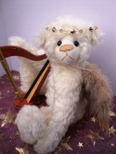 Angelique - A Heavenly Angel.  Approximately 16 inches.  Comes complete with harp and music box which plays Hark the Herald Angels Sing.  Finally she is adorned with a Swarkskovi crystal halo.  $150.00. Christmas Shows, Angels In Heaven, Harp, Heavenly, Plays, Singing, Teddy Bear, Crystal, Box