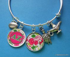 This is a Delta Zeta Charm Bracelet Bangle. The bangle was designed to show your Delta Zeta sorority pride. This beautiful silver bangle comes with five charms. A The first charm is your Lilly print charm. a turtle, and a lantern, The middle charm you may personalize with Sis, Big Sis, or Lil Sis. The last charm are your Greek letters All the products I sell are Greek licensed which means a portion of each sale goes directly to your Delta Zeta sorority. More charms of any sort may be added…
