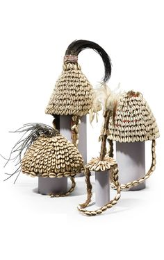 Africa | 3 'mwami' (headdresses) and 1 'kanyomwa' from the Lega people of DR Congo | Conical natural fiber cap entirely covered with cowrie shells and elephant hair and the 'kanyomwa' has feathers on top.