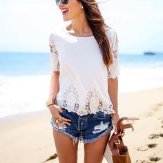 Summer vibes in a white lace top and jean shorts.