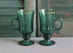 Pair of Libbey emerald green glass Irish coffee mugs with gold trim on top.  Dimensions: 5.75 tall, 3 across (not inc. handle)  Note: Gold trim may