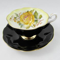 Beautiful bone china tea cup and saucer set by Royal Albert. Teacup and saucer are black with large yellow roses. Gold trimming on cup and saucer edges. Excellent condition (see photos). The markings read: Royal Albert Bone China England Milady Series Please bear in mind that these are