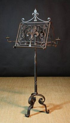 An Century French Wrought Iron Lectern. The apex top ornamented with fleur-de-lis and scrollwork and having two retractable pricket arms. Raised on a tripod base. 65 ins cms) high, 20 ins cms) wide, ins cms) deep.