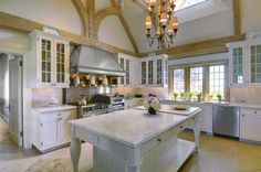 Cottage Kitchen with Flat panel cabinets, Exposed beam, High ceiling, Chandelier, Complex Granite, Stainless Steel, Skylight
