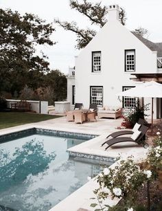 gorgeous white stucco house with black trim. modern bohemian outdoor patio and pool.