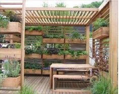 A deck is semi-enclosed with this breezy construction for boxed plants, and overhead slats for growing vines eventually to provide some shade.