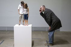 """A visitor looks at a sculpture entitled """"Young Couple, 2013"""" by artist Ron Mueck during the press day for his exhibition at the Fondation Cartier pour lart contemporain in Paris April 15, 2013. The exhibition will run from April 16 to September 29, 2013. (Photo by Charles Platiau/Reuters)"""