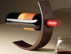 'Le Arc' as its called, isn't the shape of this wine bottle holder clearly amazing? This is beyond doubt ultra modern way to showcase your wine of the week, month or a day! It's made of poplar wood and available in 3 colors mahogany, black. Bottle Display, Bottle Rack, Wine Bottle Holders, Glass Holders, Wood Wine Holder, Wood Wine Racks, Woodworking Projects Diy, Wood Projects, Wine Storage