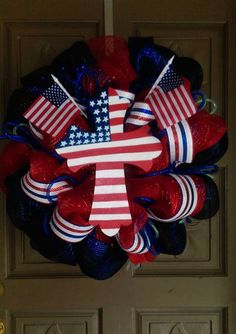 """This is a 24"""" patriotic deco mesh wreath. It is made of red, white and blue mesh and accented with patriotic ribbons and a hand painted flag cross. ALL custom wreaths and hand painted glassware ships"""