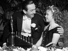 Shirley Temple presents Walt Disney with a special Oscar for Snow White And The Seven Dwarfs