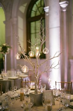 silver tree with candlelit globes hanging from it as centerpiece at reception