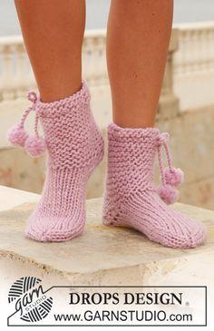 """DROPS socks in """"Eskimo"""" with pompoms."""