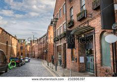 Cobbled Street Lined with Renovated Brick Buildings - stock photo