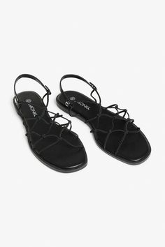 154b7379cf9 A pair of open toe black sandals with a flat sole, featuring a knotted  design