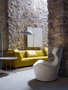 = yellow sofa and stone walls = B & B Italia