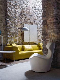 Stone walls, yellow sofa white chair